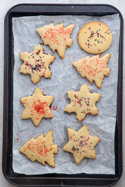 baked sugar cookies on a black cookie sheet