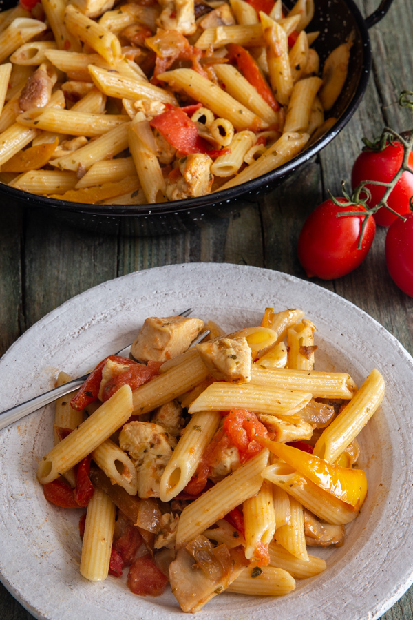 chicken pasta in a white plate and in a black skillet