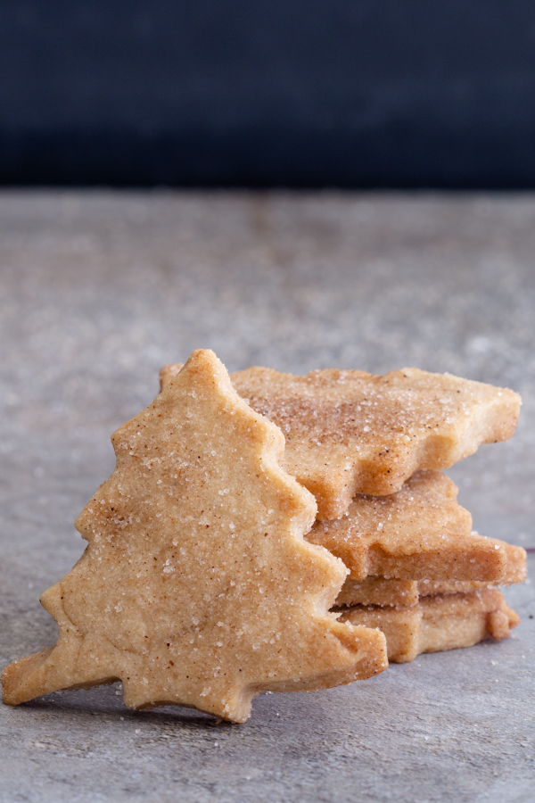 christmas tree cinnamon shortbread leaning against 4 stacked cookies