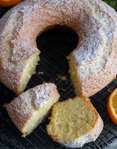 orange cake with 2 slices cut on a wire rack