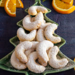 orange crescent cookies on a green tree plate with orange slices