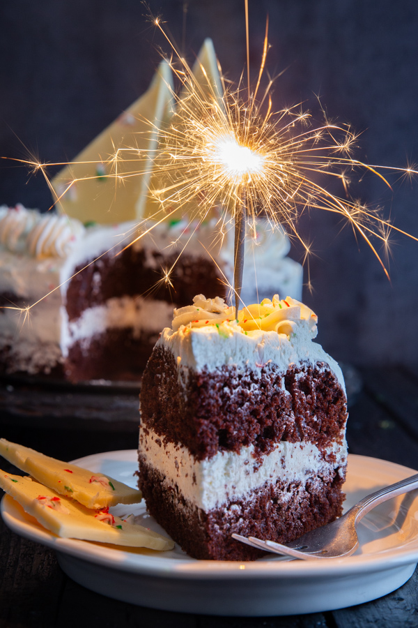 a slice of cake on a plate with a sparkler on top