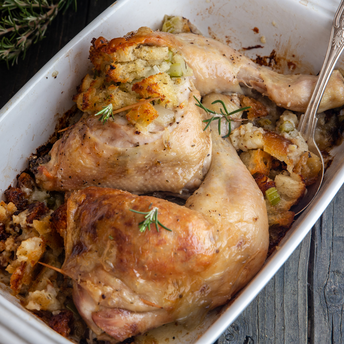 2 whole chicken legs with stuffing in a white pan