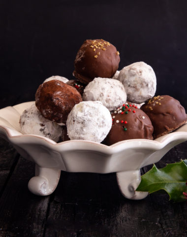 rum balls in a white plate on a black board