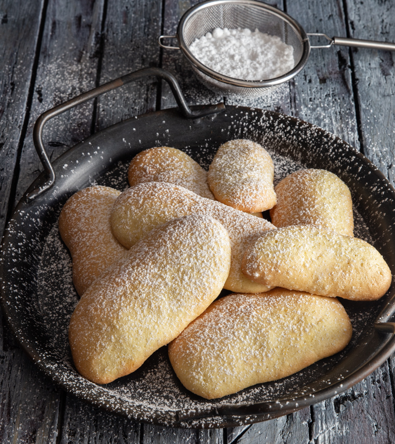 savoiardi on a black plate with powdered sugar in a small sifter