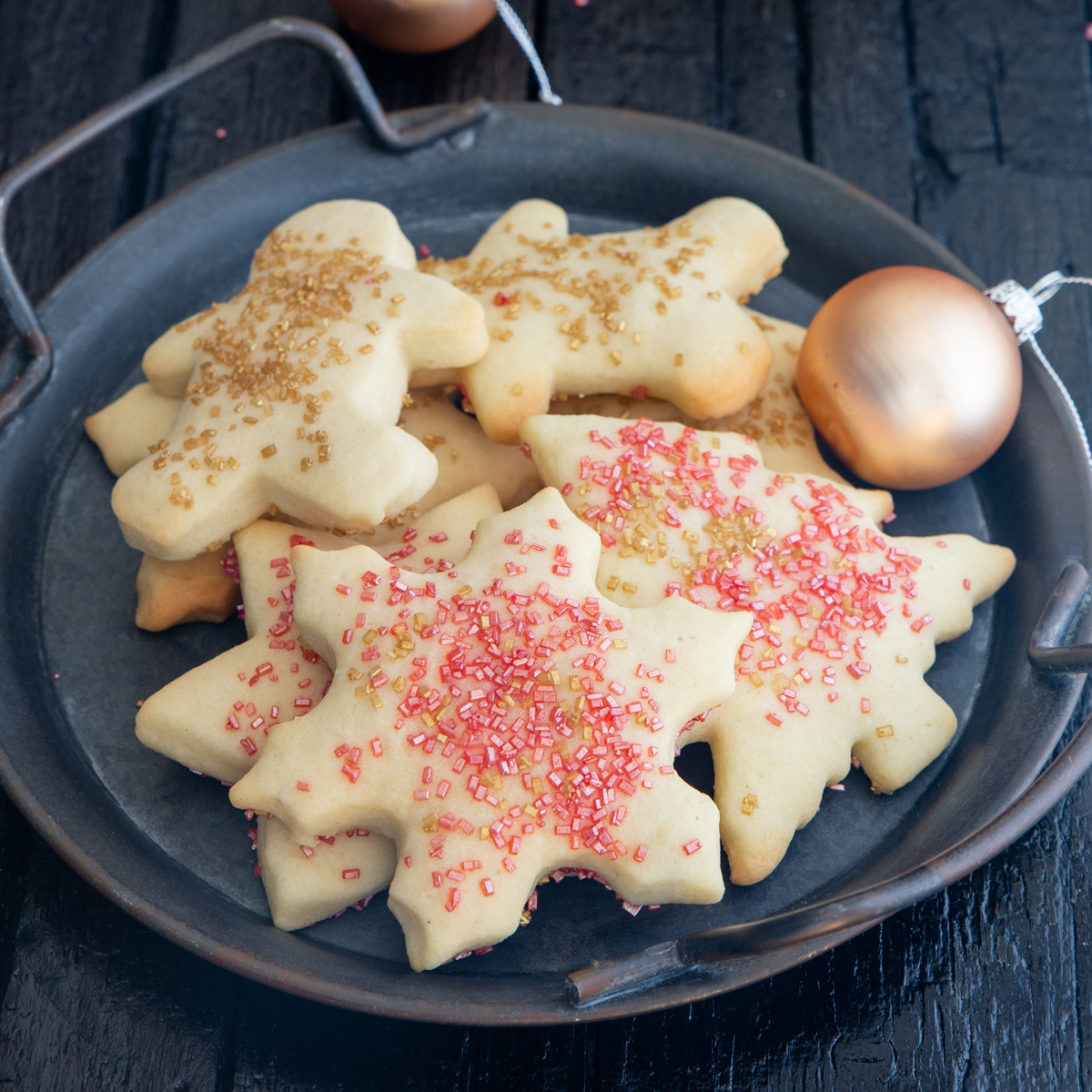sugar cookies on a black plate with fairy lights and Christmas tree balls