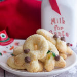 twist cookies on a snowman plate with a milk jug in the back ground