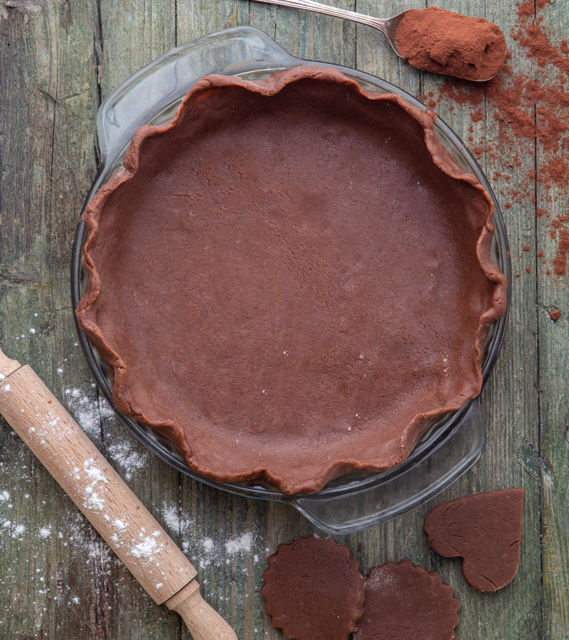pastry dough in a pie plate with a spoon of cocoa & rolling pin
