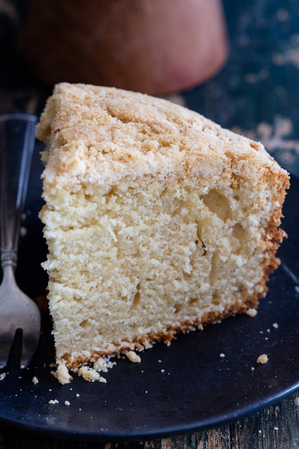 a slice of crumb cake on a black plate