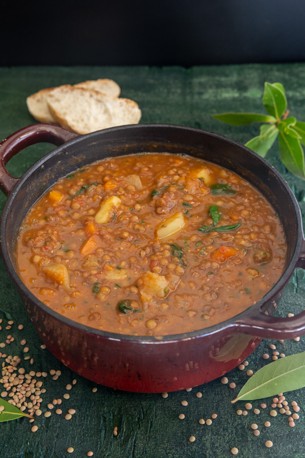 lentil soup in a red pot with 2 slices of bread on the board