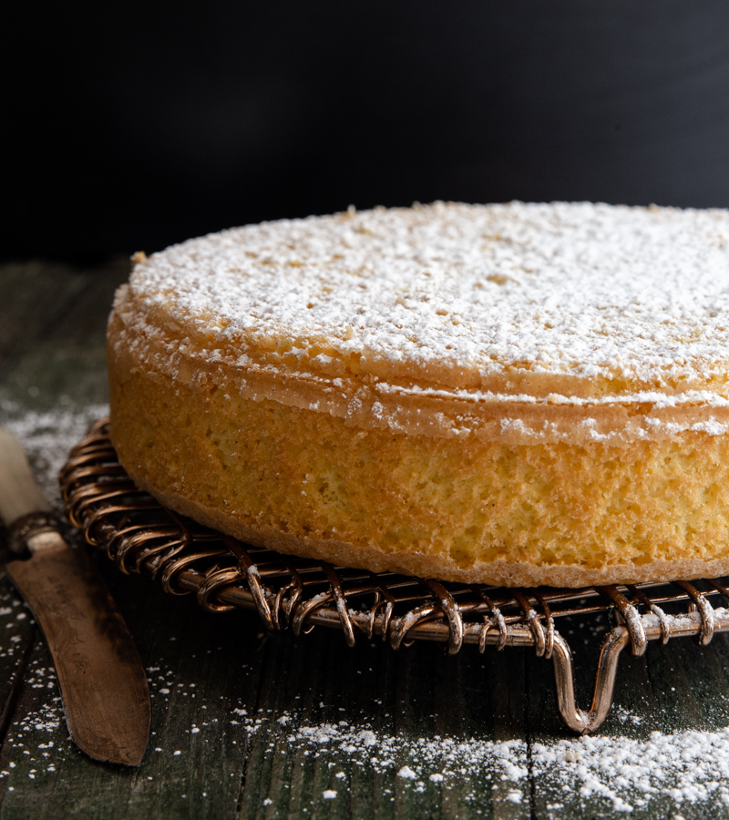 sponge cake dusted with powdered sugar on a wire rack