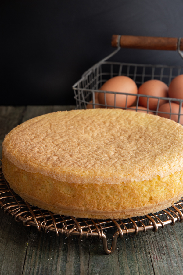 sponge cake on a wire rack with eggs in basket in the background