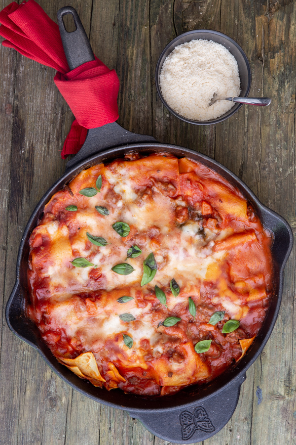 lasagna in the skillet with a small bowl of parmesan cheese and a spoon