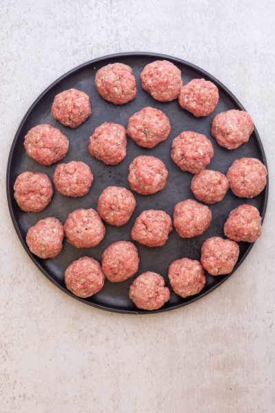 meatballs formed on a black plate