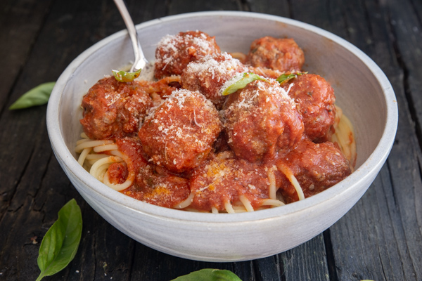 meatballs with parmesan cheese on top of pasta in a white bowl