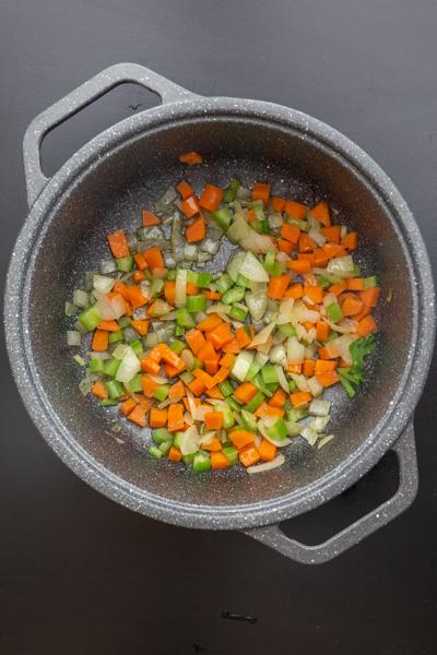 प्याज़ के पारभासी होने तक एक काले बर्तन में सब्जियाँ