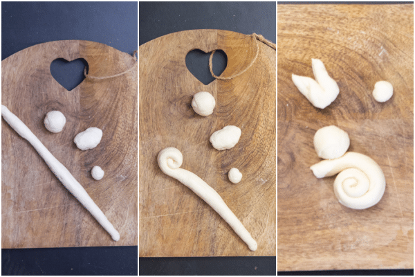 forming the dough into the shape of a bunny. A piece of dough rolled to a rope, 2 balls and ears.