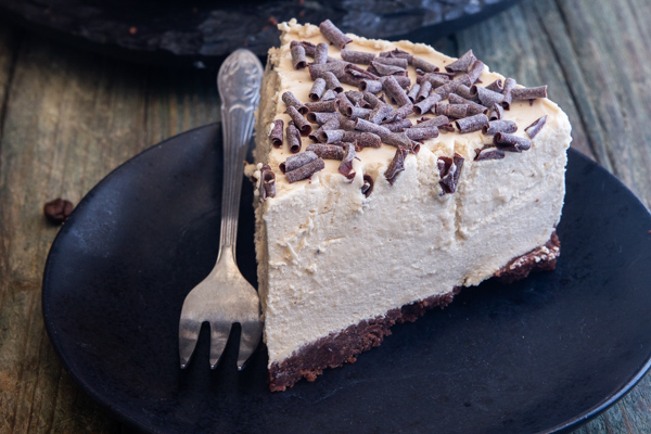 a slice of coffee cheesecake on a black plate