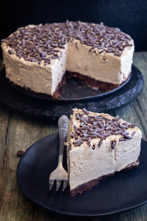 coffee cheesecake on a black stand with a slice on a black plate