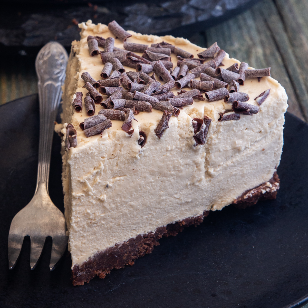 a slice of coffee cheesecake on a black plate with a fork.