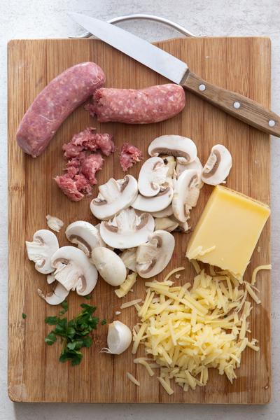 लकड़ी के बोर्ड स्ट्रूडल, सॉसेज, कटा हुआ मशरूम, कटा हुआ पनीर और मसालों के लिए सामग्री