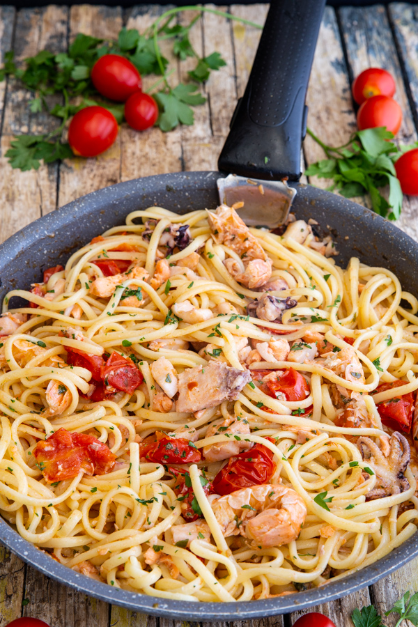 seafood pasta in a black pan.