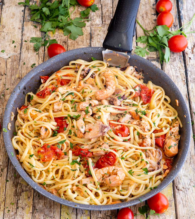 seafood pasta in a black pan, with grape tomatoes around it.