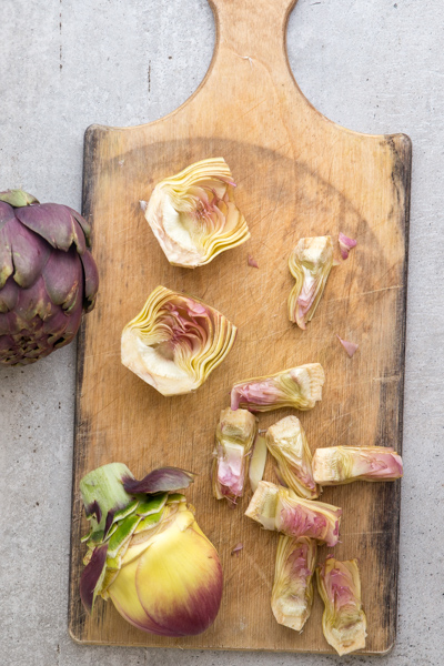 cleaning artichokes on a wooden board.