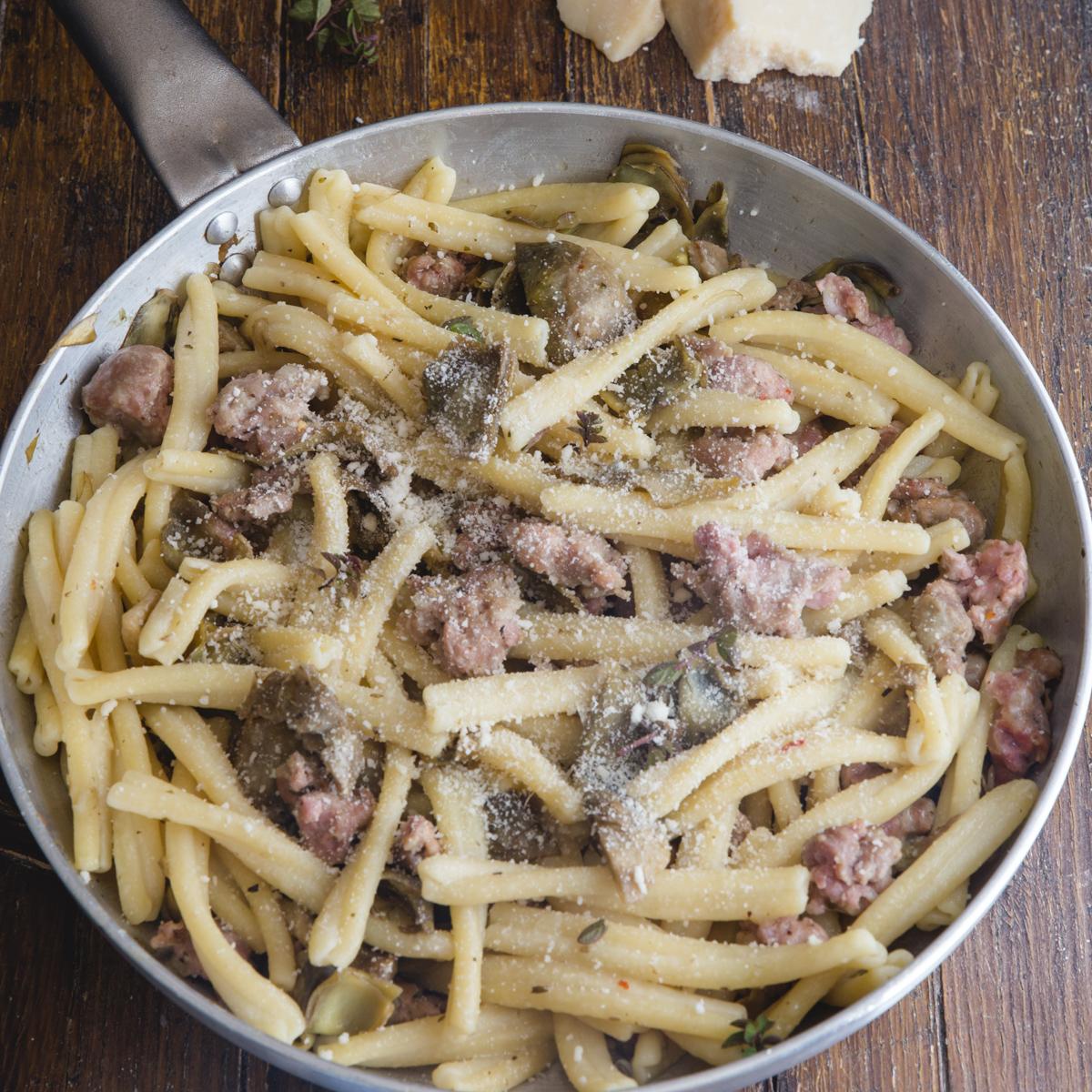artichoke & sausage pasta in a silver pan.