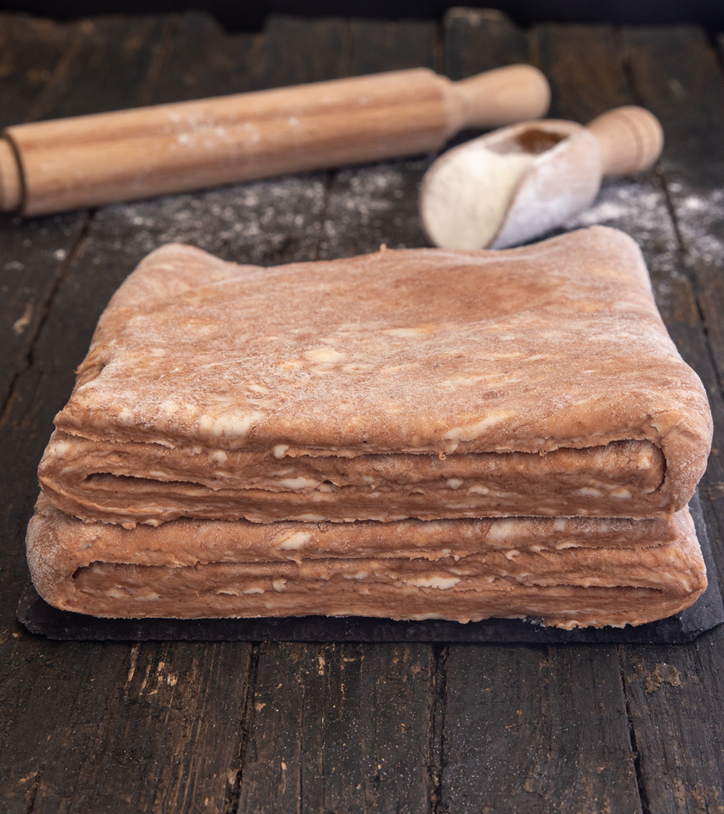 puff pastry with a rolling pin and small scoop of flour on a brown board.