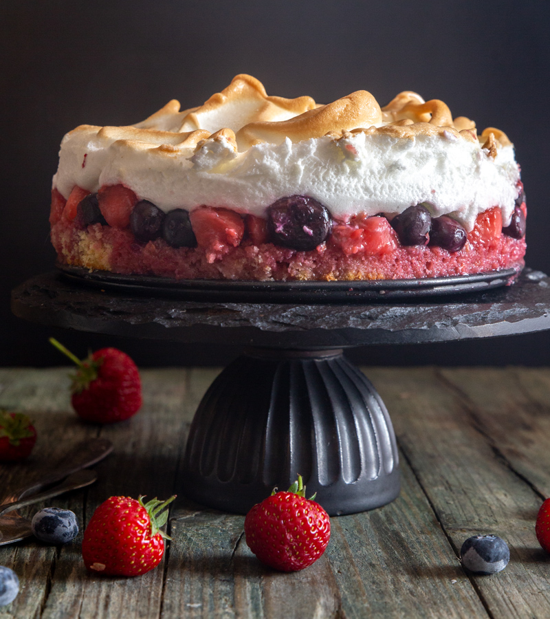 meringue cake on a black cake stand.