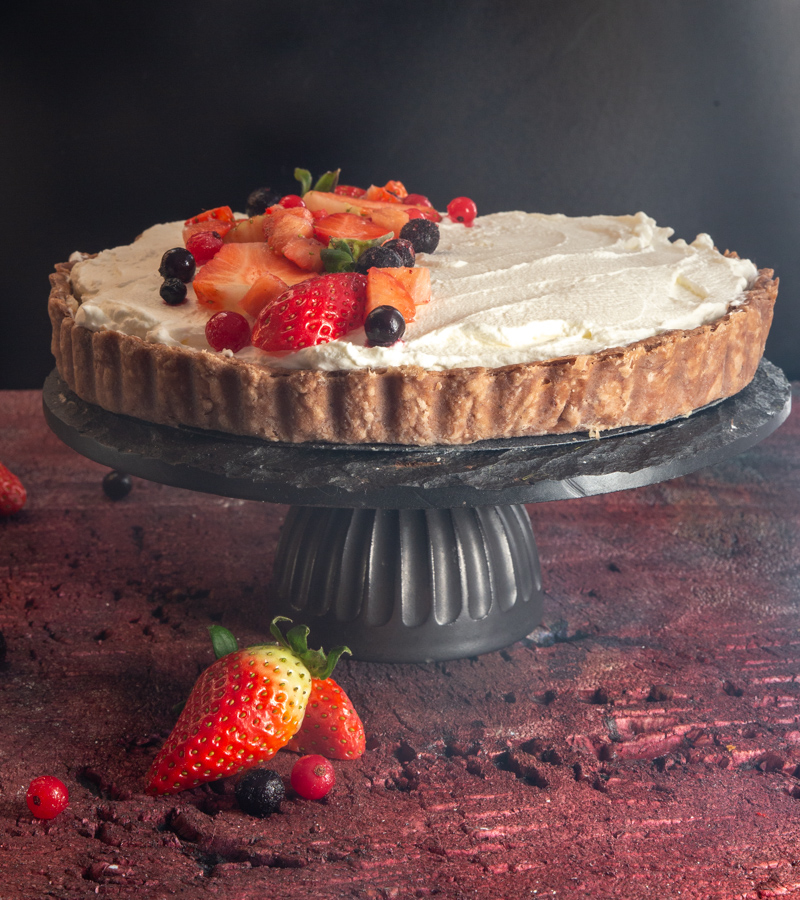 strawberry pie on a black cake stand on a red board.