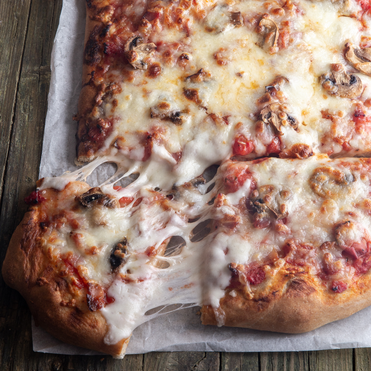 pizza on parchment paper with a slice cut.