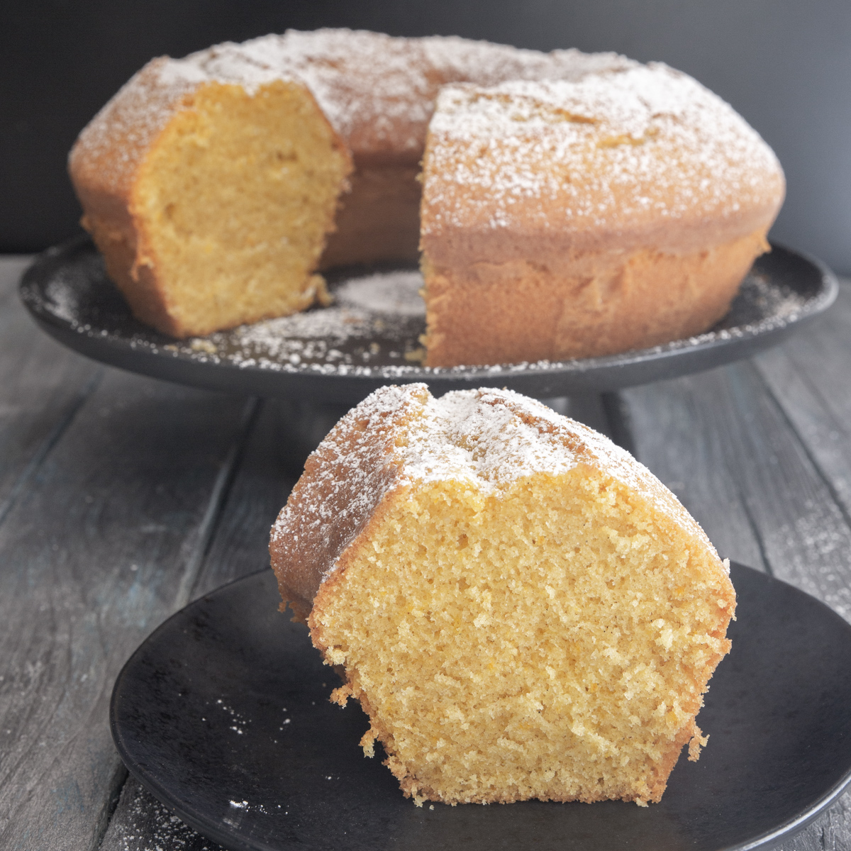 Bundt cake on a black stand with a slice cut.