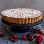 Cherry crumb pie on a blue board with cherries around it.