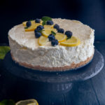 lemon cheesecake on a black stand.