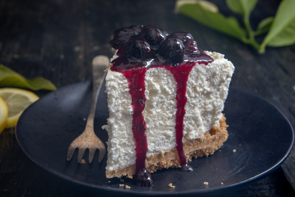 a slice of cheesecake with blueberry topping on a black plate with a fork.