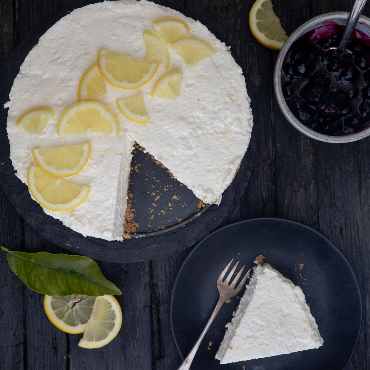 lemon cheesecake on a blackplate and a piece on a black plate.