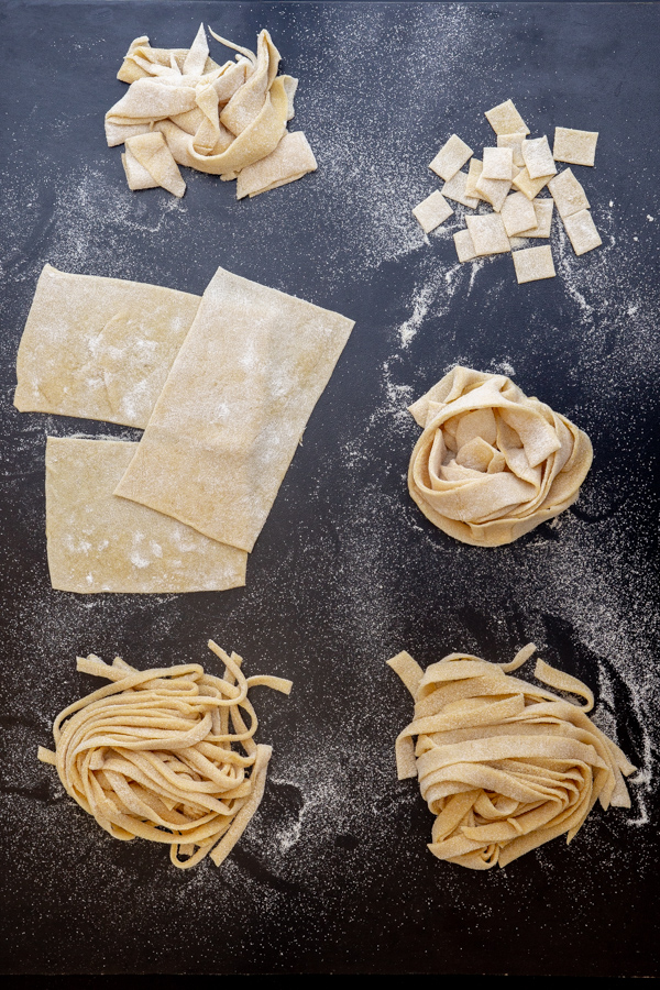 Different types of pasta on a black board.