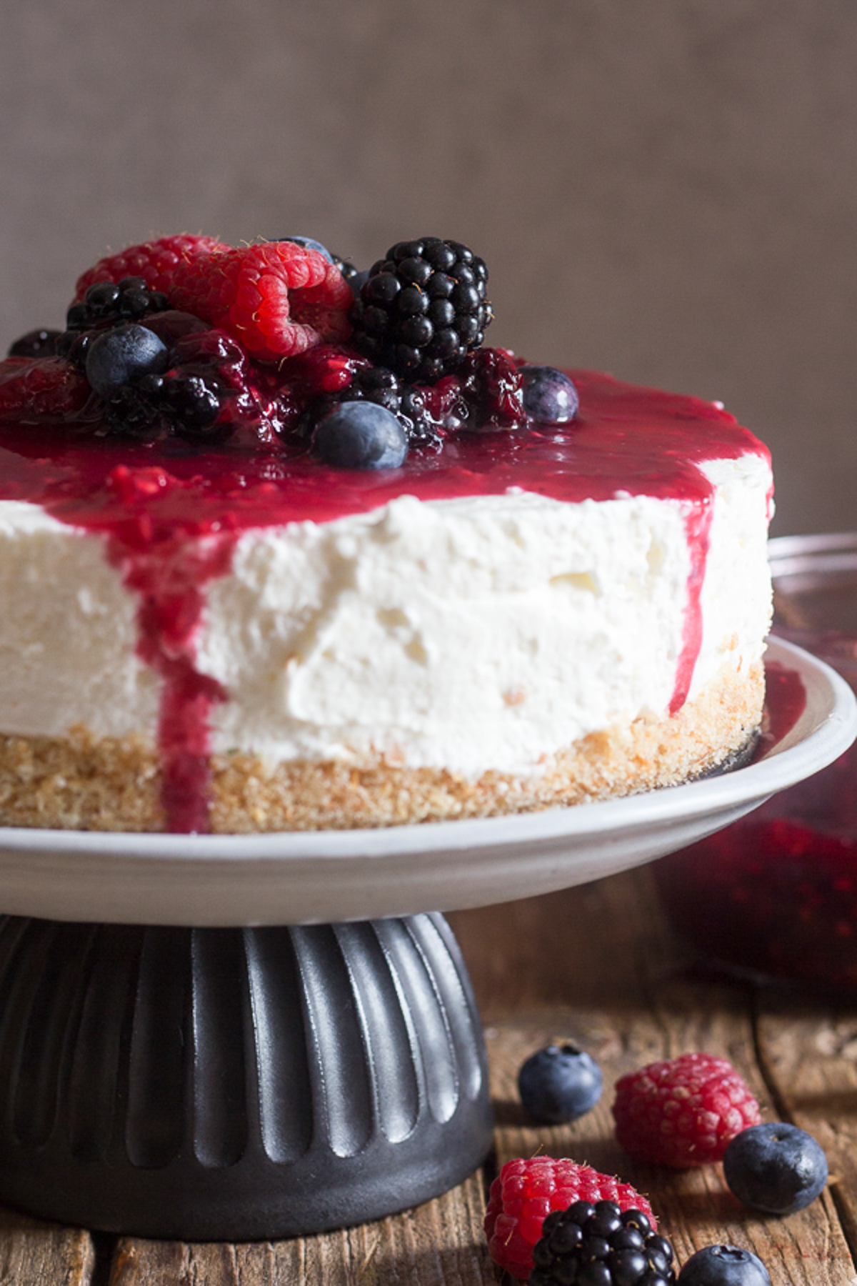Berry cheesecake on a white cake stand.