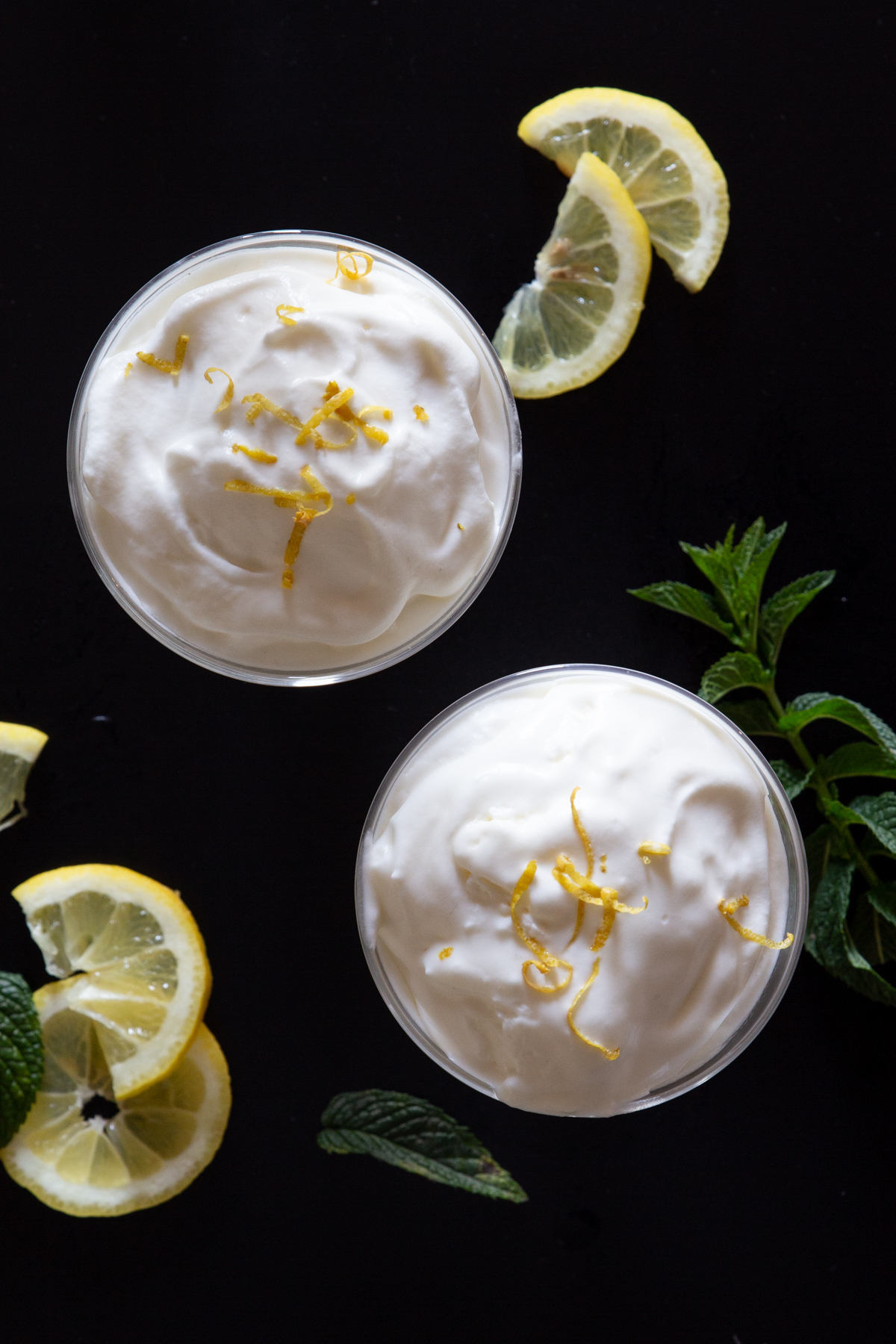 Limoncino in 2 glasses with slices of lemon.