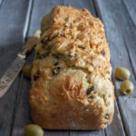 olive bread with olives and a knife on a blue board.