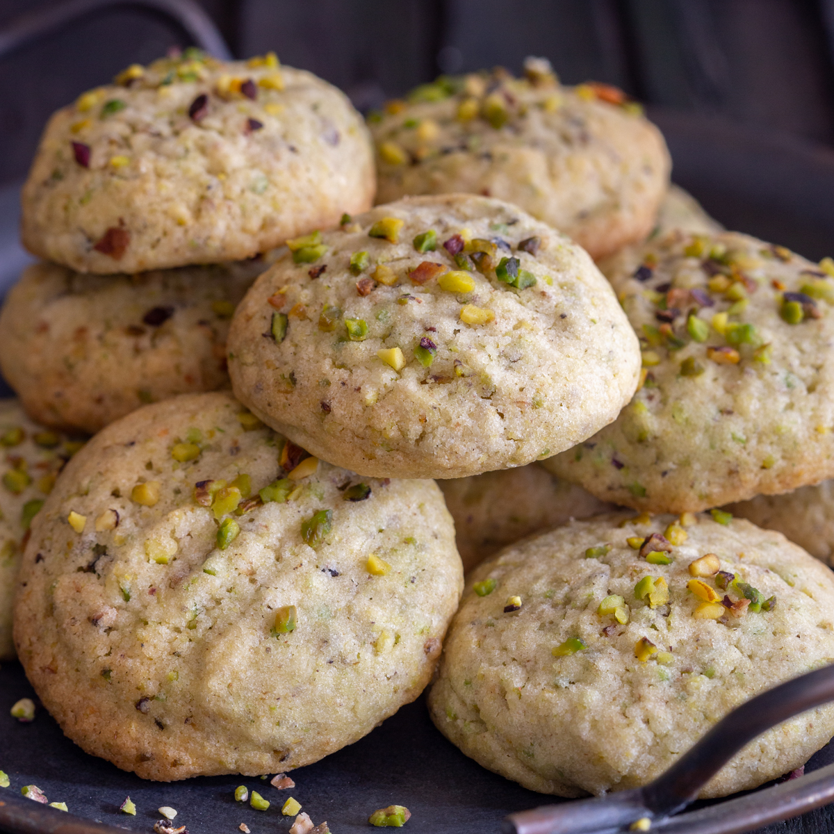 Pistachio cookies on a black tray.