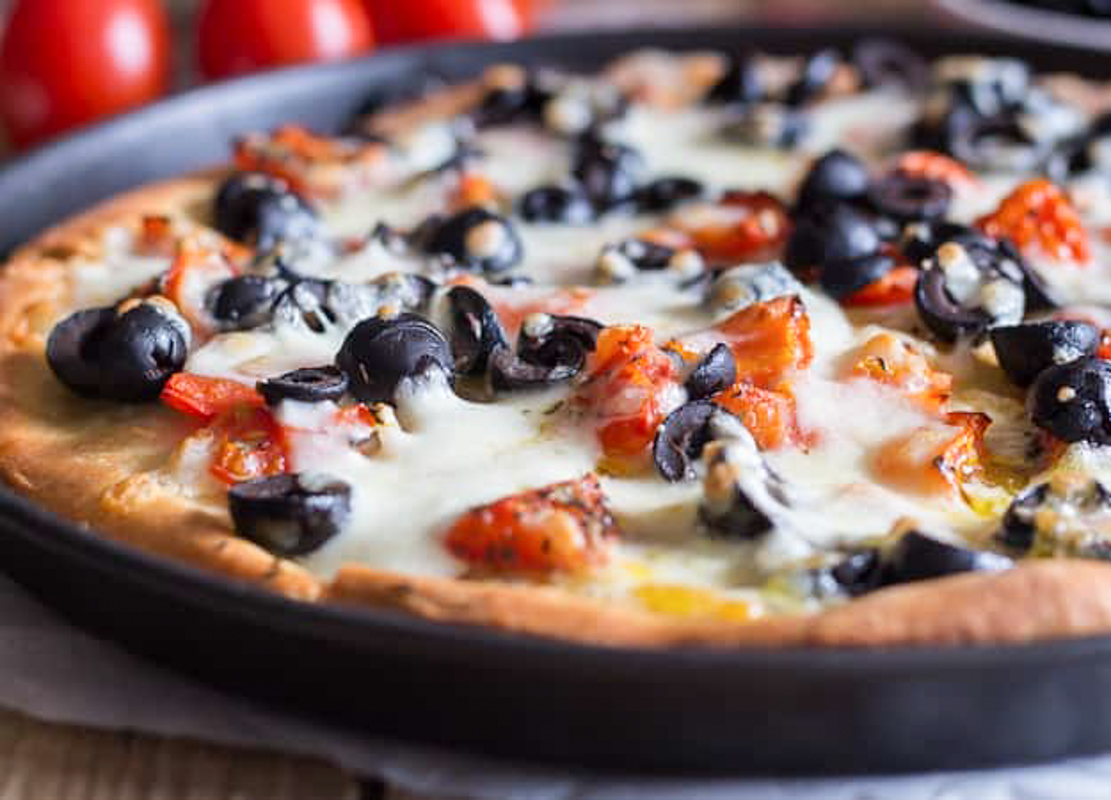Pizza with olives in the pan.