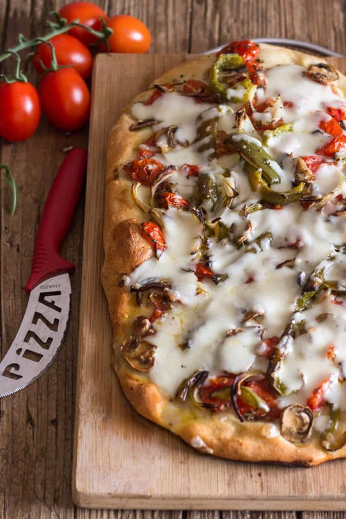 Baked pizza on a wooden board.