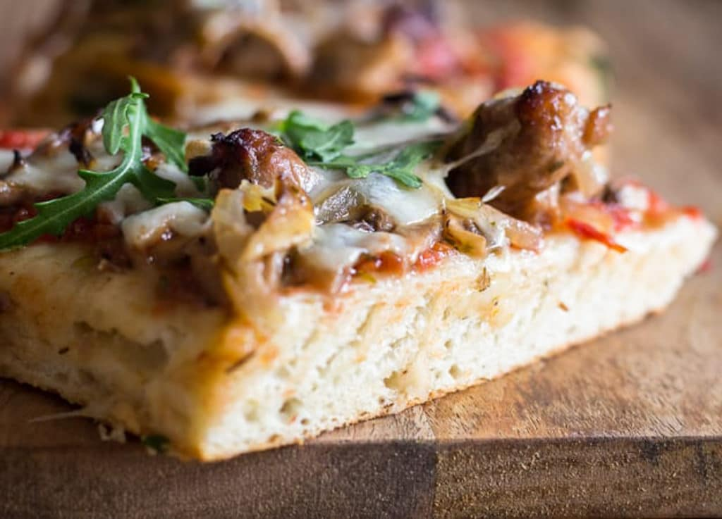 A slice of mushroom pizza on a wooden board.