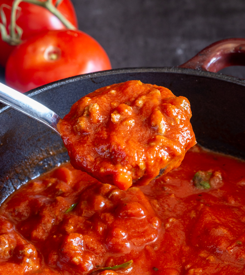 Sauce in a ladle over the pot of sauce.