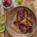 Sun dried tomatoes in a brown dish and a glass jar.