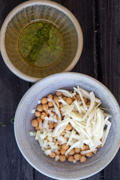 Olive oil mixture mixed in a biege bowl and chickpeas & fennel in a blue bowl.