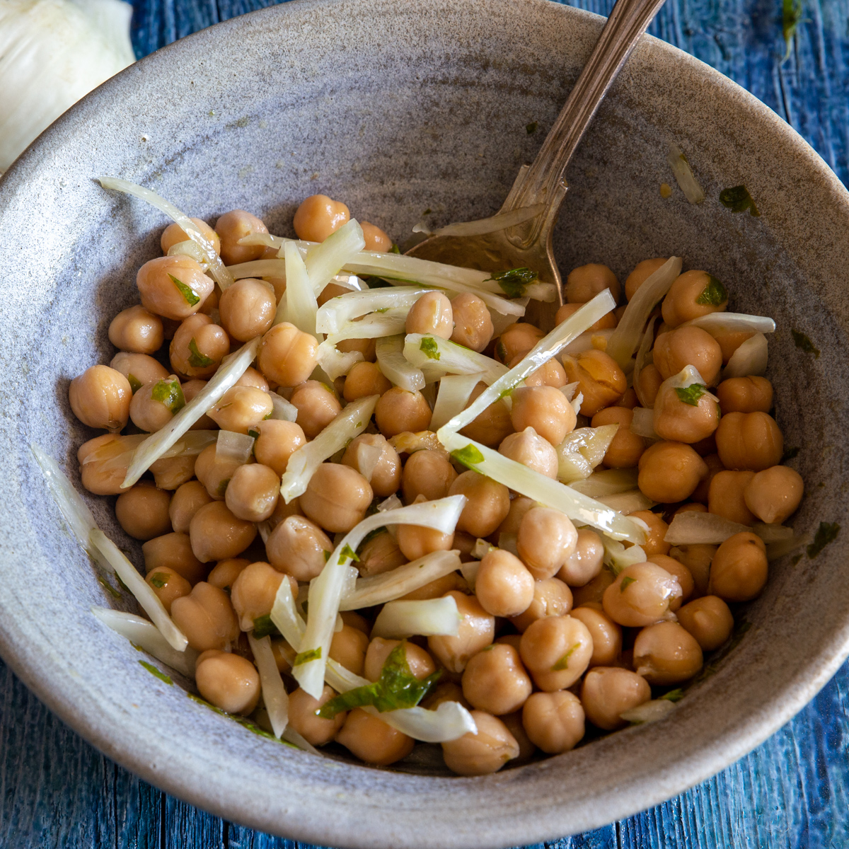 Chickpeas salad in a grey bowl with a silver spoon.
